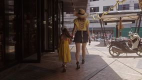 黄色礼服的女孩去有他的母亲的把柄在街道下 爱在晴朗的家庭生活方式 股票录像