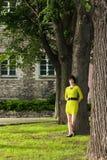 黄色礼服的女孩在一个结构树倾斜在公园 库存图片