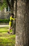 黄色礼服的女孩在公园拥抱一个结构树 免版税库存照片