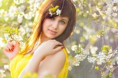 黄色礼服的女孩在樱花的春天 免版税库存图片