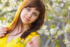 黄色礼服的女孩在樱花的春天 免版税库存照片