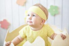 黄色礼服的小女孩有在蛋壳的头饰带的 库存图片