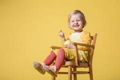 黄色礼服的年轻女婴在黄色背景 免版税图库摄影