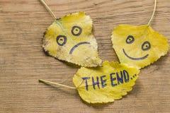 黄色离开与一张愉快和哀伤的面孔和题字的图片末端 图库摄影