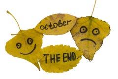 黄色离开与题字10月,末端和一张哀伤的满足的面孔 孤立 库存图片