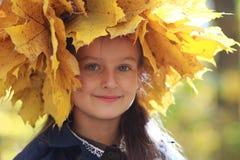 黄色秋叶花圈的女孩  库存图片