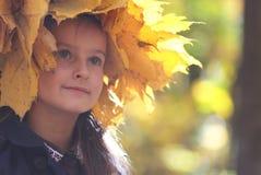 黄色秋叶花圈的女孩  免版税库存图片