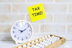 黄色稠粘的笔记写与& x27选择聚焦; 税时间! & x27;使用算盘和台式时钟 企业和财务题材 免版税图库摄影