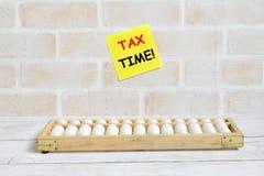 黄色稠粘的笔记写与& x27选择聚焦; 税时间! & x27;使用算盘 企业和财务题材 库存图片