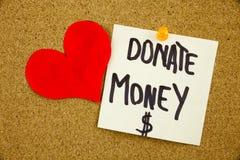 黄色稠粘的笔记文字,说明,题字词组捐赠在黑ext的金钱在稠粘的笔记被别住对黄柏布告牌 免版税库存图片
