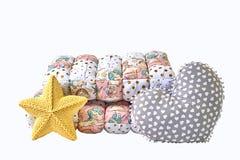 黄色编织了五针对性的星状枕头、补缀品橡皮奶嘴和心形的枕头在白色背景 图库摄影