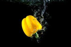 黄色胡椒和明亮的水飞溅 健康和鲜美食物 免版税库存照片