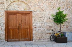 黄色自行车和木盆有一棵树的对一个石墙有一个大木门的 库存照片