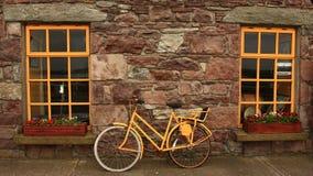 黄色自行车对石墙和黄色窗口 图库摄影