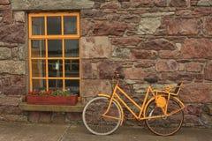黄色自行车对石墙和黄色窗口 库存照片