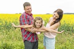 黄色花的愉快的家庭夫妇nd儿童女儿在自然在夏天 库存照片