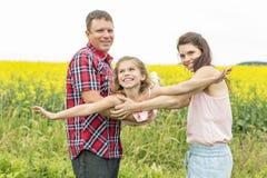 黄色花的愉快的家庭夫妇nd儿童女儿在自然在夏天 免版税库存图片