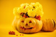 黄色花花束在南瓜的 万圣节 免版税图库摄影