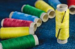 黄色螺纹短管轴与一根针的在色的螺纹短管轴背景在牛仔布的 免版税库存照片