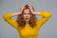 黄色衣裳的卷曲少妇紧贴到一个` s头为使烦恼 免版税库存照片