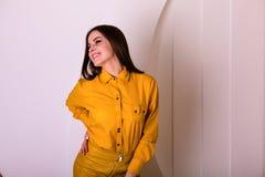 黄色衬衣和裙子的美丽的妇女 库存照片