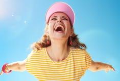 黄色衬衣的健康妇女反对蓝天欣喜 免版税库存照片