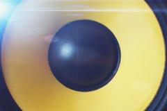 黄色超低音扬声器动态或合理的报告人有蓝色光、音乐和党背景 免版税图库摄影