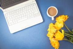 黄色郁金香、膝上型计算机和咖啡在蓝色背景反弹,夏天概念舱内甲板被放置的顶视图 免版税图库摄影