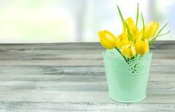 黄色郁金香的装饰构成在土气明亮木的 免版税图库摄影