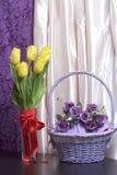 黄色郁金香花束在一条红色丝带包裹的一个玻璃花瓶站立被栓对弓 其次与花的一个柳条筐 图库摄影