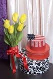 黄色郁金香花束在一条红色丝带包裹的一个玻璃花瓶站立被栓对弓 附近有有礼物的箱子 免版税库存照片