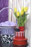 黄色郁金香花束在一条红色丝带包裹的一个玻璃花瓶站立被栓对弓 附近有有礼物的箱子 库存照片