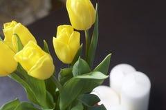 黄色郁金香花束在一条红色丝带包裹的一个玻璃花瓶站立被栓对弓 附近装饰蜡烛 特写镜头, 库存照片
