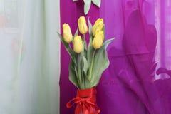 黄色郁金香花束在一条红色丝带包裹的一个玻璃花瓶站立被栓对弓 免版税图库摄影