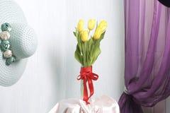 黄色郁金香花束在一条红色丝带包裹的一个玻璃花瓶站立被栓对弓 库存照片
