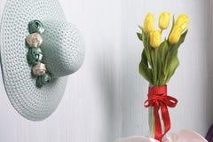 黄色郁金香花束在一条红色丝带包裹的一个玻璃花瓶站立被栓对弓 免版税库存图片
