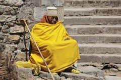 黄色长袍的修士有香客` s职员的休息 免版税库存图片