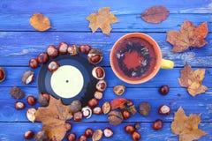 黄色陶瓷杯子清凉茶和葡萄酒唱片在年迈的木背景与秋叶和栗子 免版税图库摄影