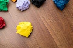 黄色顶视图弄皱了在黑褐色木头桌上的纸球 图库摄影