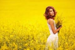 黄色领域的美丽的女孩 免版税库存图片