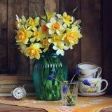 黄色黄水仙花束在蓝色玻璃花瓶的 图库摄影