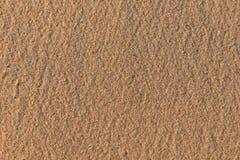 黄色,软,光滑,美好的沙子纹理与琥珀色的芯片的在海滩 免版税库存照片
