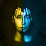 黄色-蓝色面孔可看见通过他的手 两次曝光 免版税库存照片