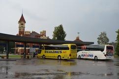 黄色Ecolines公共汽车和白色Eurolines在一个驻地在Mariampol,拉脱维亚 库存图片