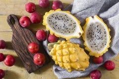 黄色pitahaya或龙果子和红色李子在木背景 免版税库存图片