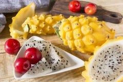黄色pitahaya或龙果子和红色李子在木背景 免版税库存照片