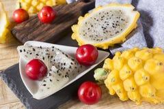 黄色pitahaya或龙果子和红色李子在木背景 库存照片