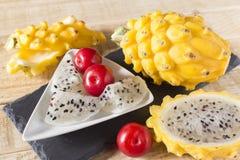 黄色pitahaya或龙果子和红色李子在木 免版税库存图片