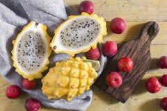 黄色pitahaya或龙果子和红色李子在木 免版税库存照片