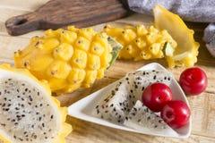 黄色pitahaya或龙果子和红色李子在木 库存图片